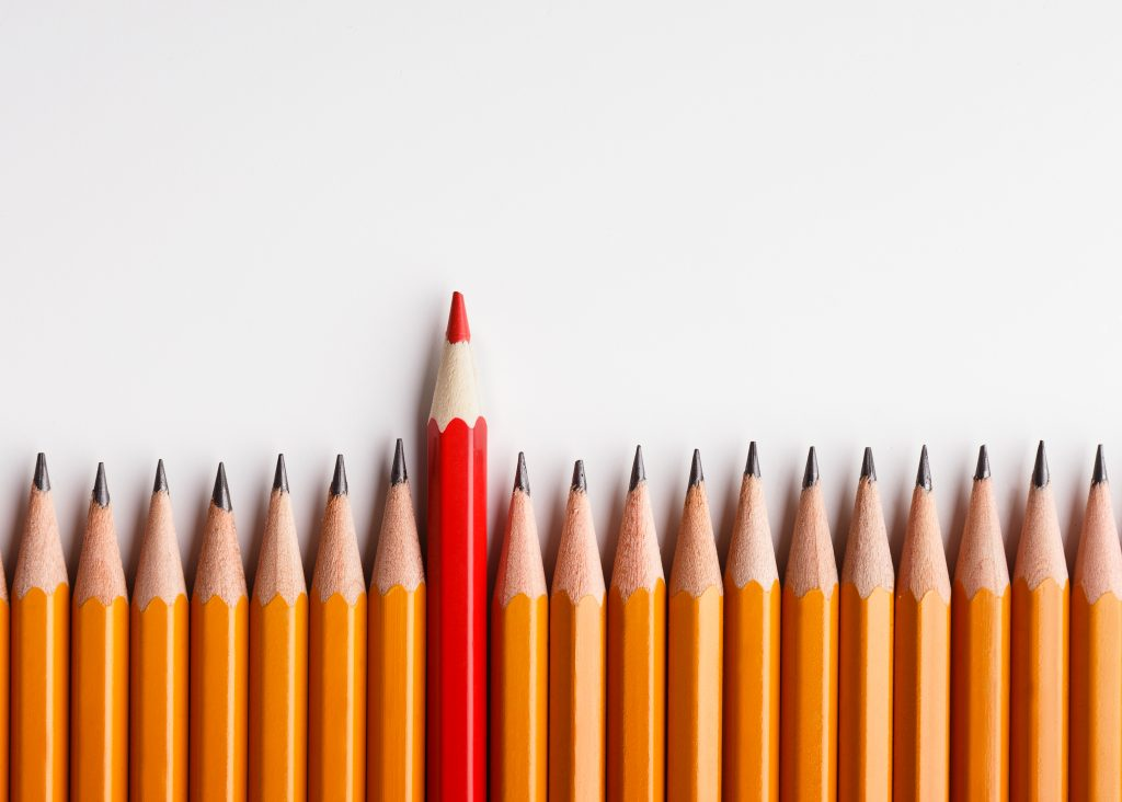 brand identity is like One red pencil standing out of line with similar ones